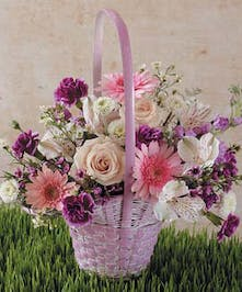 Pink handbasket filled with pink and purple flowers.