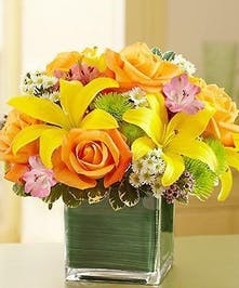 Yellow lilies, orange roses and other flowers in a green glass cube vase.