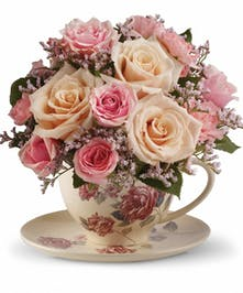 Floral teacup filled with roses, spray roses, mini carnations and more.