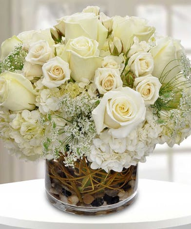 All-white flower arrangement of roses, hydrangea and Queen Anne's Lace.