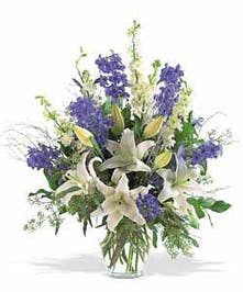 Hanukkah bouquet of blue and white flowers and greenery in a clear glass vase
