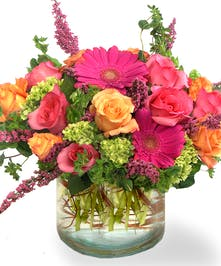 Roses, gerbera daisies, and hydrangea in a clear glass vase.
