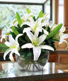 White lilies and greenery in a clear glass bowl vase.