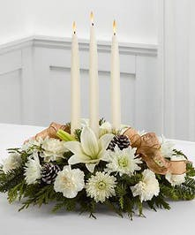 White floral centerpiece with greenery and three taper candles