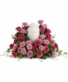 Sympathy display of light and bright pink roses arranged in a wreath to display around an urn.