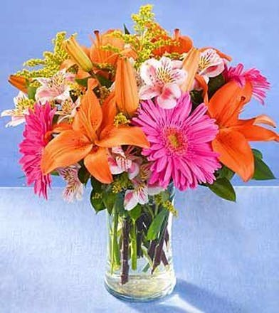 Orange lilies, pink gerber daisies and other bright flowers in clear glass vase.