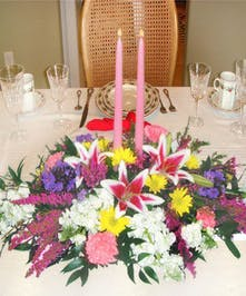Floral centerpiece of spring flowers surrounding two pink taper candles.