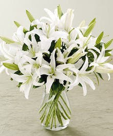 Casablanca lilies in a clear glass vase.
