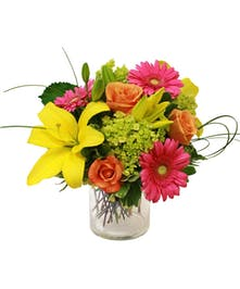 Gerbera daisies, lilies, roses and hydrangea in a clear glass vase.