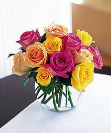 Twelve mixed colored roses in a small bubble bowl vase.