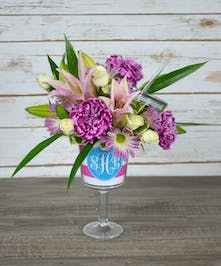 Seasonal flowers presented in a custom monogrammed wine glass.