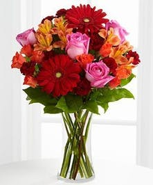 Fuchsia roses, red gerbera daisies, orange spray roses, burgundy mini carnations, peach Peruvian Lilies and greenery in a clear glass vase.