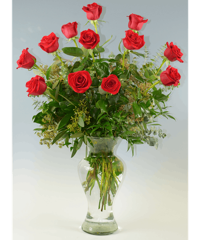 One dozen long stem red roses and greenery in a tall clear glass vase.