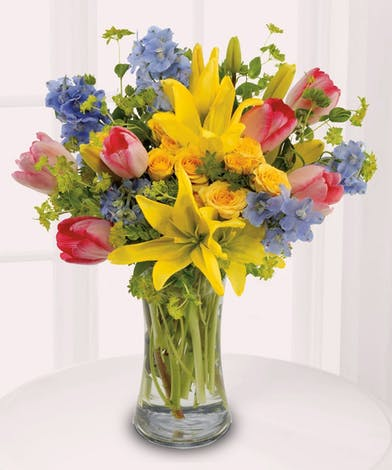 Yellow lilies, tulpis and spray roses in a clear glass vase.