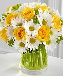 Yellow and white flowers in a clear glass vase.