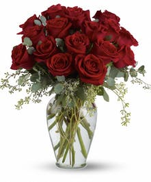 16 red roses and eucalyptus in a clear glass vase.