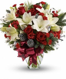 Red roses, white lilies, berries and pine in a tall arrangement.