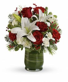 Leaf-lined vase of white lilies, red roses, seasonal greenery and berries.