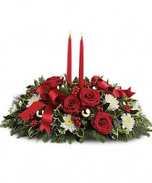Holiday centerpiece of evergreens, roses, mums, taper candles, oranments and ribbon