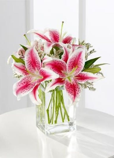 Bouquet of pink lilies in a tall glass cube vase.