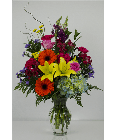 Colorful bouquet of lilies, hydrangea, daisies and more in a clear glass vase.