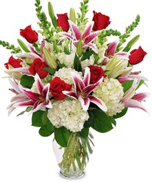 Stargazer lilies, long stem roses, white snapdragons and white hydrangea in a clear glass vase.