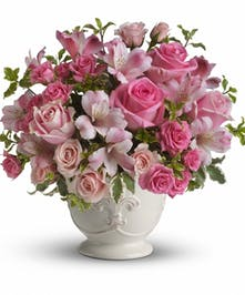 Pink alstroemeria, roses and spray roses with greenery in an elegant white container.