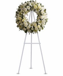 Sympathy wreath of all white flowers including roses, Asiatic lilies, carnations, mums and more.