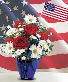 Cobalt blue vase filled with red and white flowers with a miniature American flag.