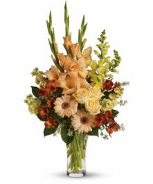 Bouquet of peach roses, gerberas, orange alstroemeria, yellow snapdragons and more in a clear glass vase.