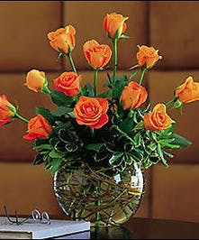 One dozen orange roses and curly willow in a bubble bowl vase.