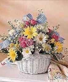 White basket filled with various color flowers and tied with a blue check ribbon.