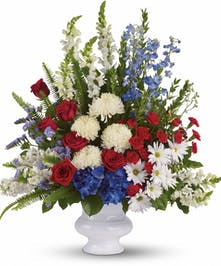 A patriotic display of red, white and blue flowers in a white urn.