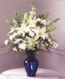 All-white flower arrangement in a tall blue vase.