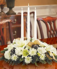 Holiday centerpiece with white lilies, carnations and chrysanthemums accented with gold ribbon and holiday greenery