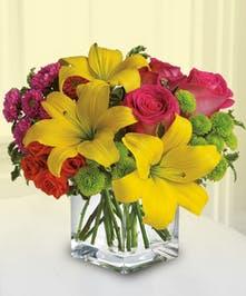 Yellow, pink, red and green flowers in a clear glass cube vase.