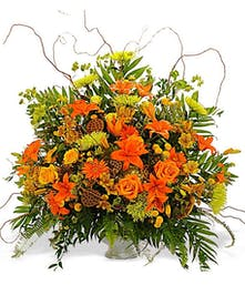 Sympathy arrangement of orange and green flowers with greenery presented in an urn.