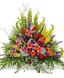 Sympathy arrangement of vivid blue, orange, red and green flowers with greenery.