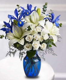 Blue and white flowers and greenery in a bright blue vase