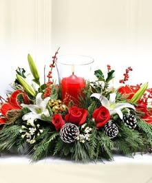 Holiday centerpiece of evergreens, roses, lilies and pine cones with a pillar candle and glass hurricane